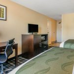 Two Queen Bed Ends across from Desk, Chair, Dresser, and TV at Quality Inn & Suites Albany